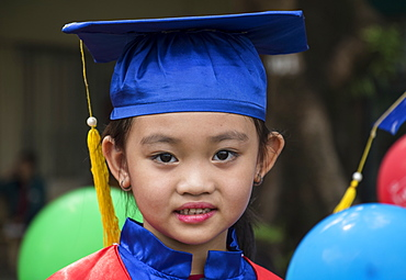 Portrait of a Vietnamese school girl in a cap and gown for graduation, Ho Chi Minh City, Vietnam