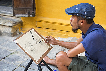 Man painting on the street in the Old Quarter, Hoi An, Quang Nam, Vietnam
