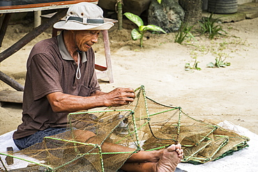 Fisherman sitting and repairing a net, Hoi An Ancient Town, Quang Nam, Vietnam