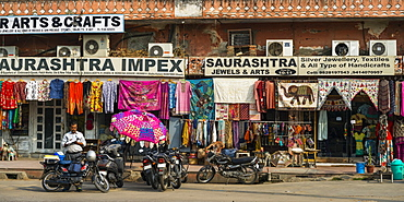 Shops along a street with colourful textiles hanging on display, Jaipur, Rajasthan, India