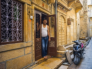 An Indian man stands in the doorway of his home with a motorcycle parked outside, Jaisalmer, Rajasthan, India