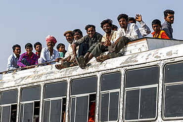 A bus full of people and passengers riding on the roof, Jaisalmer, Rajasthan, India