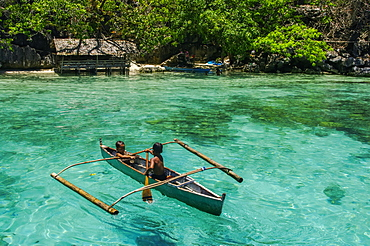Boys paddling in an outrigger canoe, fishing in the turquoise waters of the Indian Ocean, Andaman Islands, India