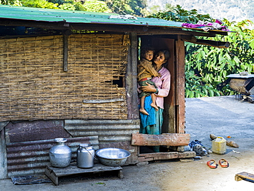 An Indian mother holds her young son in the doorway of their home, Bhalu Khop Village, Sikkim, India