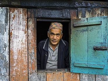 Portrait of an Indian man looking out a window, Radhu Khandu Village, Sikkim, India