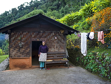 A woman stands outside her home in Radhu Khandu village, Sikkim, India