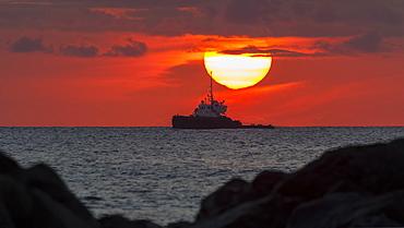 Tugboat in sunset viewed from Magic Island, Ala Monana beach park, Honolulu, Oahu, Hawaii, United States of America