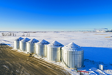 Aerial view of snow-covered large metal grain storage bins in a snow-covered field with blue sky, South of Calgary, Alberta, Canada