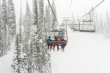 Skiers on a chairlift at Sun Peaks ski resort during a snowfall, Kamloops, British Columbia, Canada