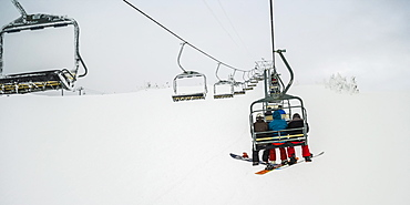 Skiers on a chairlift at Sun Peaks ski resort, Kamloops, British Columbia, Canada