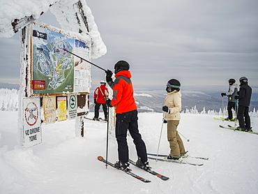 Skiers look at a map at Sun Peaks ski resort, Kamloops, British Columbia, Canada