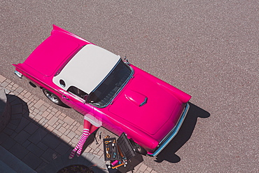 A pink Thunderbird being repaired by a woman, composite image