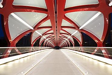 Glowing lights inside a pedestrian red metal bridge at night, Calgary, Alberta, Canada
