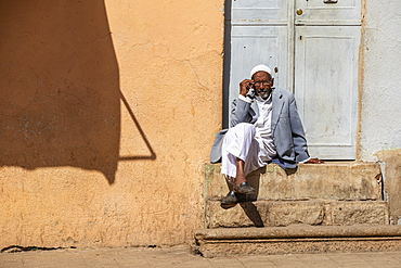 Eritrean man sitting on steps outside a door, Asmara, Central Region, Eritrea