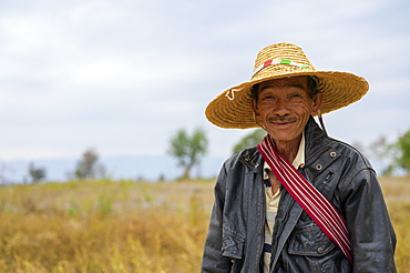 A farmer standing in a field wearing a straw hat, Taungyii, Shan State, Myanmar
