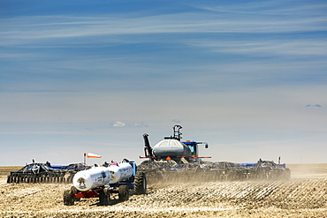 Air seeder in field with white ammonia tanks, near Beiseker, Alberta, Canada