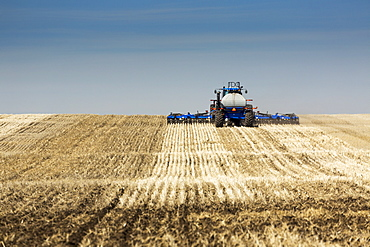 Back view of air seeder, seeding a stubble field with blue sky and hazy clouds, near Beiseker, Alberta, Canada