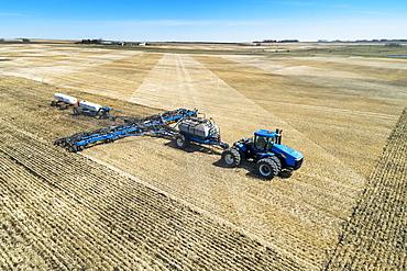 Air seeder in field with white ammonia tanks, near Beiseker, Alberta, Canada