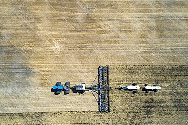 Aerial view of air seeder in field with white ammonia tanks, near Beiseker, Alberta, Canada