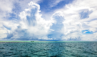 Turquoise water of the Pacific Ocean with a cloud-filled big sky overhead, Malolo Island, Fiji
