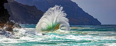 Large ocean wave crashes into rock along the Na Pali Coast, Kauai, Hawaii, United States of America