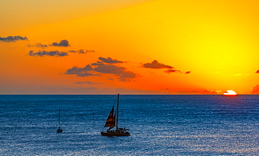 Sunset over the ocean with sailboats off Waikiki Beach, Honolulu, Oahu, Hawaii, United States of America
