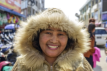 Woman wearing a warm, fur-trimmed coat at the market, Lashio, Shan State, Myanmar