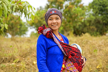 Young mother standing with her baby in a sling, Taungyii, Shan State, Myanmar