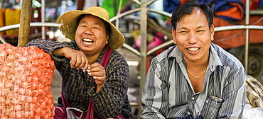 Man and woman sit laughing while at the market, Taungyii, Shan State, Myanmar