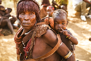Hamer woman carrying a baby at a bull jumping ceremony, which initiates a boy into manhood, in the village of Asile, Omo Valley, Southern Nations Nationalities and Peoples' Region, Ethiopia