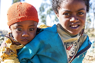 Ethiopian girl carrying a little boy, Simien Mountains, Amhara Region, Ethiopia