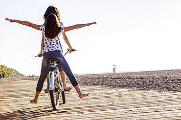 Two friends riding tandem on a bike together with bare feet down a wooden boardwalk along Woodbine Beach, Toronto, Ontario, Canada
