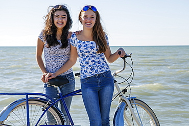 Two teenage girls posing with a bike on Woodbine Beach, Toronto, Ontario, Canada