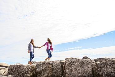 Two teenage girls holding hands as they walk along boulders, Woodbine Beach, Toronto, Ontario, Canada