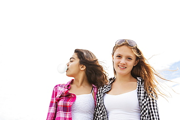 Two friends standing together with windblown hair, one blowing a bubble with bubblegum, Toronto, Ontario, Canada
