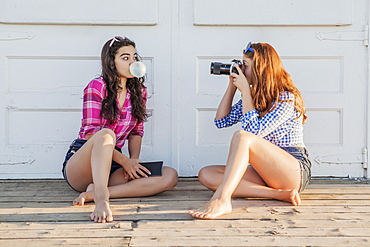 Teenage girl taking a picture of a friend blowing a bubble with bubblegum, Toronto, Ontario, Canada