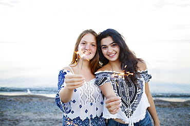 Two friends holding sparklers at Woodbine Beach, Toronto, Ontario, Canada
