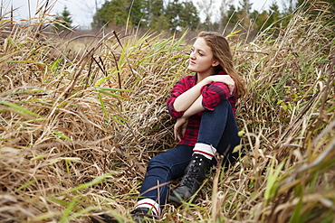 Portrait of a girl sitting in a field of tall grass looking away from the camera, Toronto, Ontario, Canada