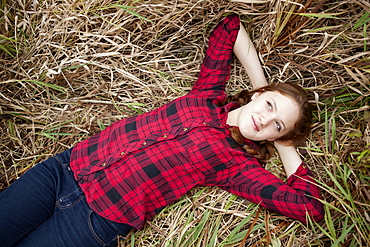 Portrait of a girl lying in a field of tall grass looking up, Toronto, Ontario, Canada