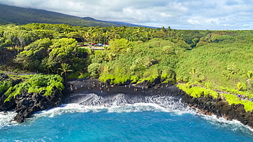Tourists on the black sand beach at Waianapanapa State Park, Hana, Maui, Hawaii, United States of America