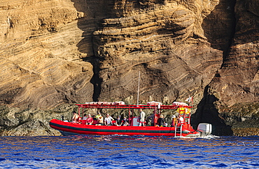 Snorkelers getting ready to enter the water from a snorkelling tour boat operated out of Maui, Hawaii. They are located next to the backwall of Molokini Crater which is a volcanic tuff cone, Maui, Hawaii, United States of America