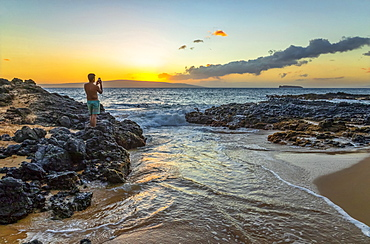 A young man in a bathing suit stands on the volcanic rock on the shore capturing the golden sunset with a smart phone camera, Kihei, Maui, Hawaii, United States of America