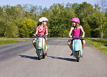 Two girls riding electric scooters down a paved country road, Canada
