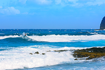 A surfer on the breaking waves close to the shore of Kaupo Cove, with bright blue water and sky on the horizon, Oahu, Hawaii, United States of America