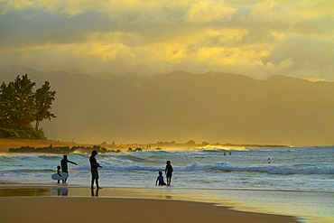 Silhouette of surfers on Kelki Beach with dramatic glowing clouds above at sunset, Oahu, Hawaii, United States of America