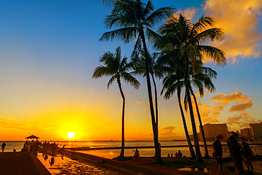 Tourists along the waterfront of Waikiki at sunrise with a golden sun rising above the ocean, Honolulu, Oahu, Hawaii, United States of America