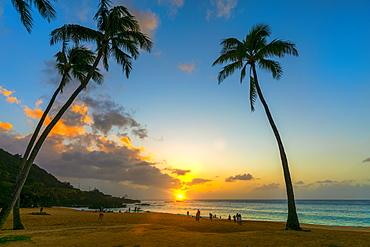 Tourists enjoying the beach at Waimea Bay Beach Park at sunset, Oahu, Hawaii, United States of America