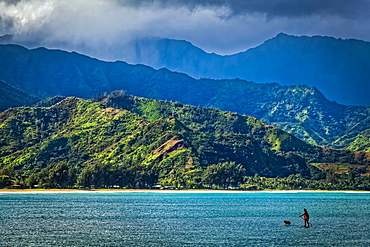 A man and his dog on a stand up paddle board in Hanalei Bay with mountains in background, Hanalei, Kauai, Hawaii, United States of America