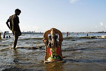 A Ganesha idol washes ashore in Mumbai, Maharashtra, India, Asia