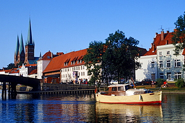 Boat in front of St. Marien church and St. Petri church, Lubeck, Schleswig-Holstein, Germany